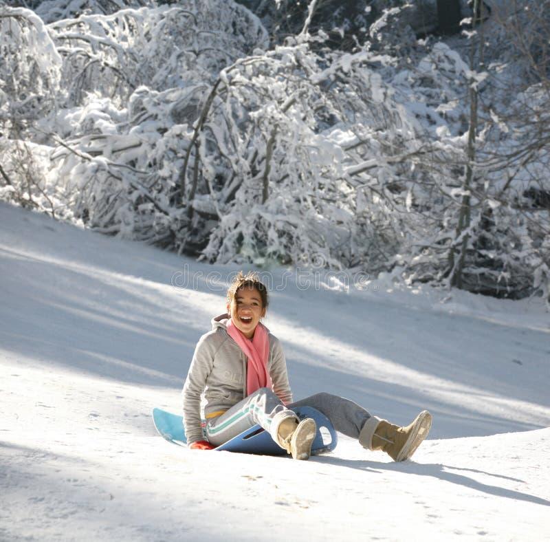 Girl on a sled. Teenage girl enjoying her sled ride royalty free stock photo