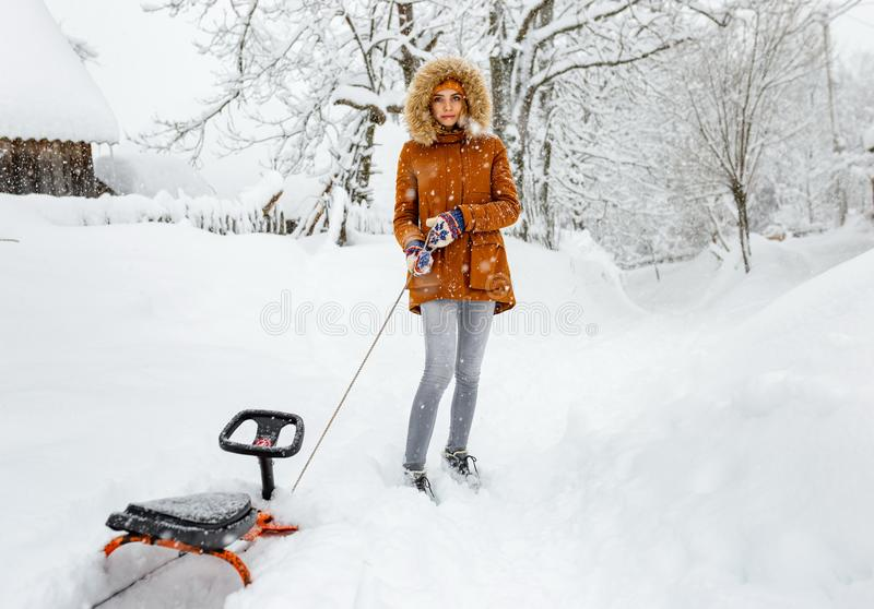 Girl sled alone on snow outdoor, winter cold weather, outside sledge countryside blizzard a snowfall stock images