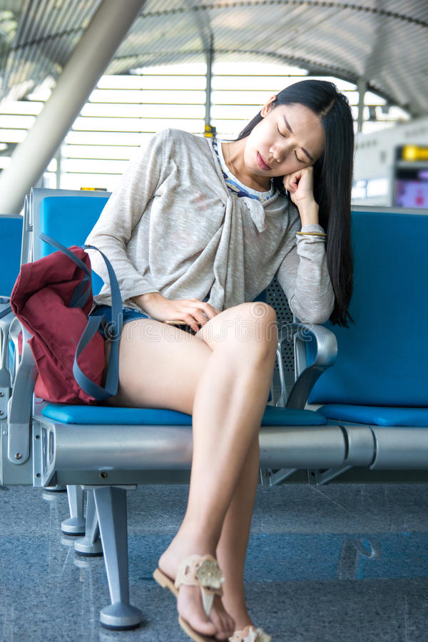 Girl sleeping in airport waiting hall stock photography
