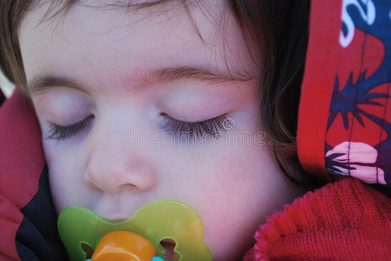 Girl sleeping in a backpack with a pacifier stock photo