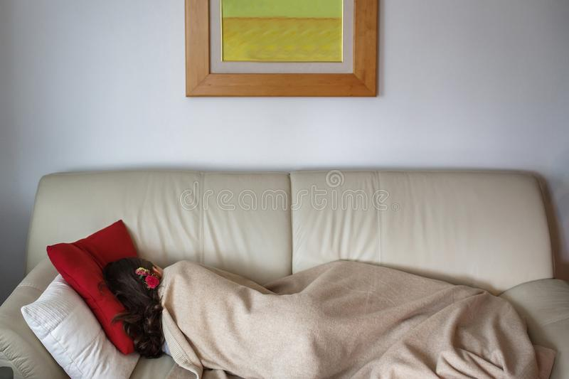The girl is sleeping on the couch stock photos