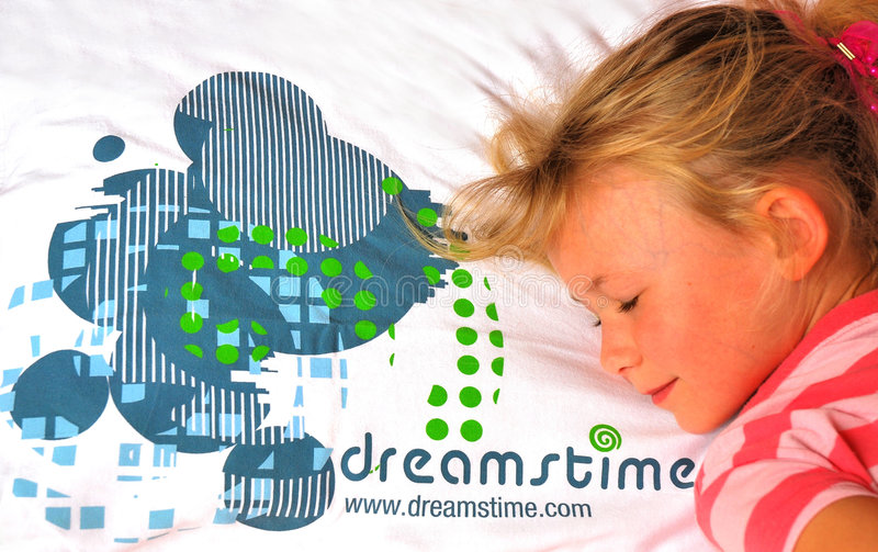Girl sleeping on Dreamstime pillow. Portrait of a cute little caucasian girl child sleeping and dreaming on her Dreamstime pillow stock image