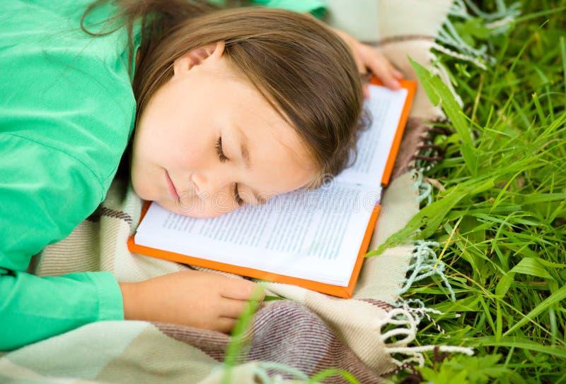 Girl is sleeping on her book outdoors. Little girl is sleeping on her book outdoors royalty free stock photo