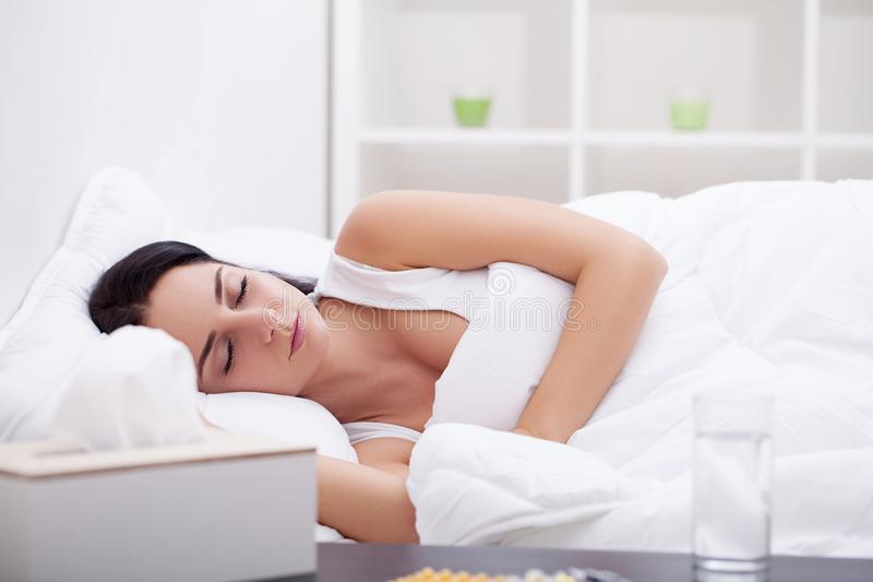 Girl sleeping in late on weekend tired from long work week resting on plush white comforter stock photos