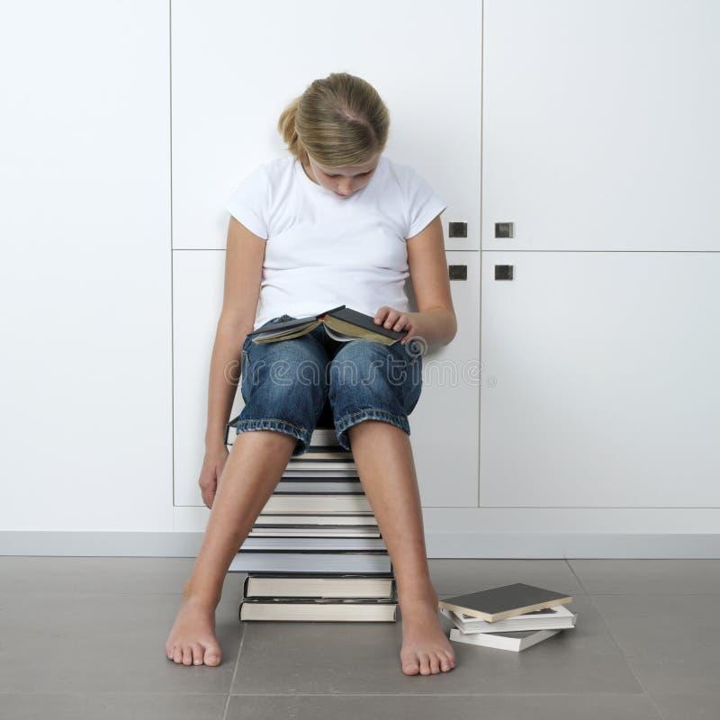 Girl sleeping over her books stock photo
