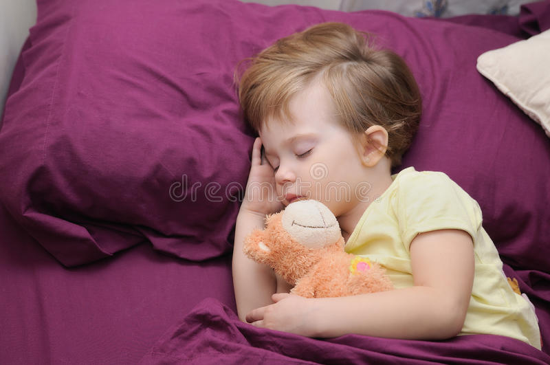 Girl sleeping peacefully with her teddy bear on the bed. Girl sleeping peacefully with her teddy bear between garnets sheets royalty free stock images