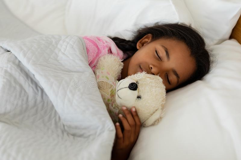 Girl sleeping with teddy bear in bed in bedroom royalty free stock images