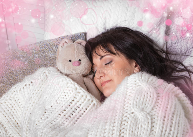 Girl sleeps in a bed with a toy a teddy bear royalty free stock images