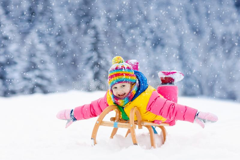 Girl on sleigh ride. Child sledding. Kid with sledge. Little girl enjoying a sleigh ride. Child sledding. Toddler kid riding a sledge. Children play outdoors in stock images