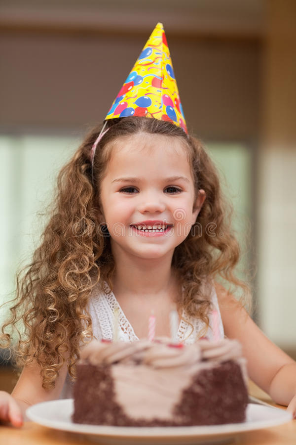 Girl with a slice of cake in front of her. Smiling girl with a slice of cake in front of her stock photos