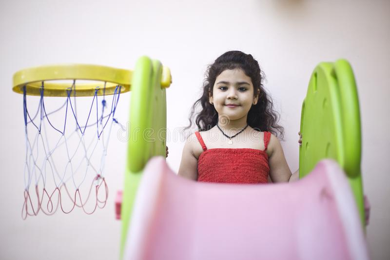 Girl with slide and basketball hoop. Portrait of little girl with playing slide and basketball hoop royalty free stock photo