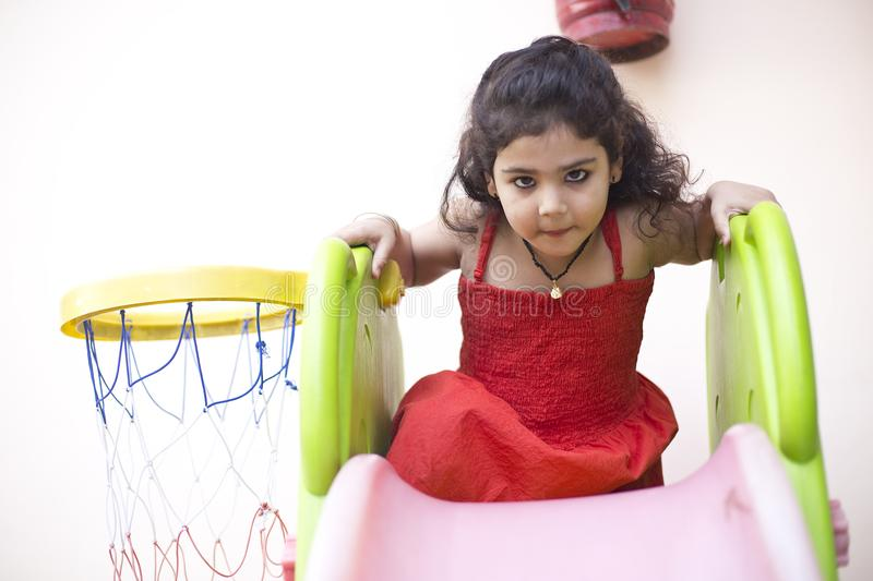 Girl with slide and basketball hoop. Portrait of little girl with playing slide and basketball hoop stock photo