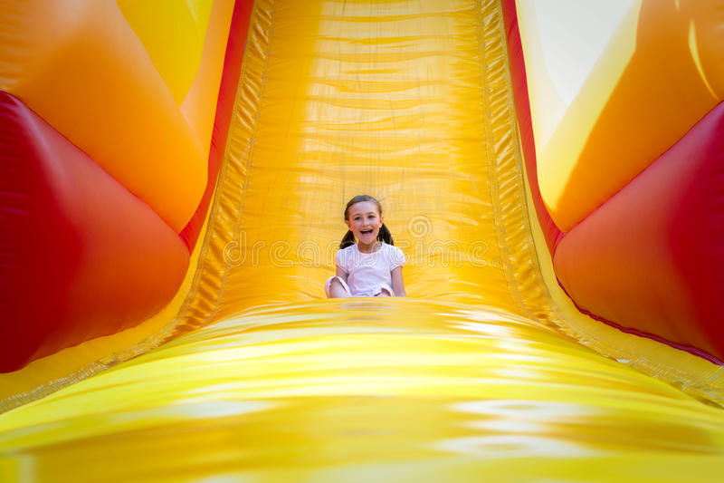 Girl on Slide. Happy little girl having lots of fun on a jumping castle while sliding stock photography