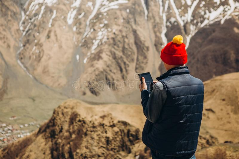 Girl smartphone mountain beautiful landscape range snow. Girl with a smartphone is standing on a mountain with a beautiful landscape of a mountain range with royalty free stock image
