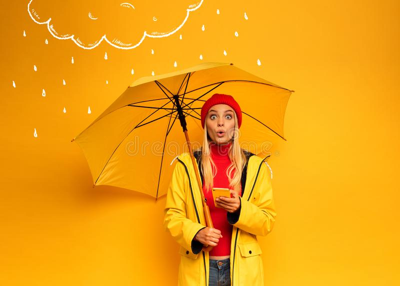 Girl with smartphone and umbrella on yellow background surprised for the weather royalty free stock images