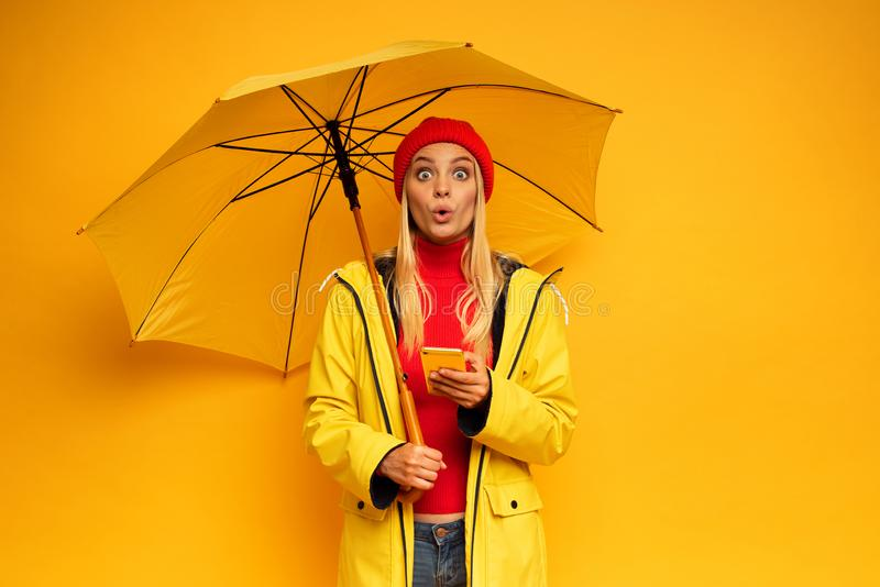 Girl with smartphone and umbrella on yellow background surprised for the weather royalty free stock photos