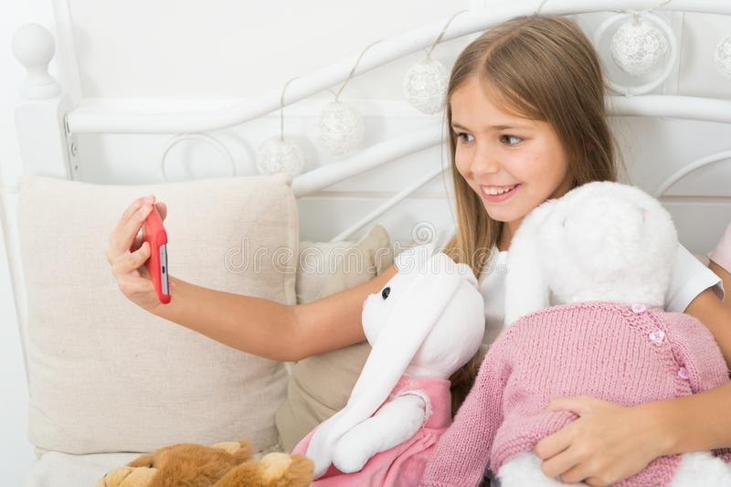 Girl with smartphone use modern technology. Selfie with favorite toy. Send selfie photo your friends social network. Kid royalty free stock image