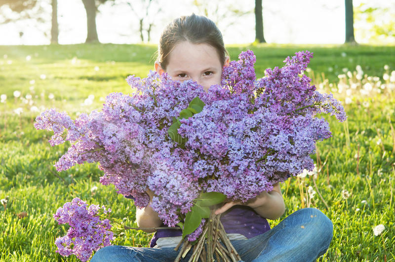 Girl smelling bouquet of Lilac flowers. Child smiles and peeks above bouquet while smelling Lilac flowers royalty free stock photo