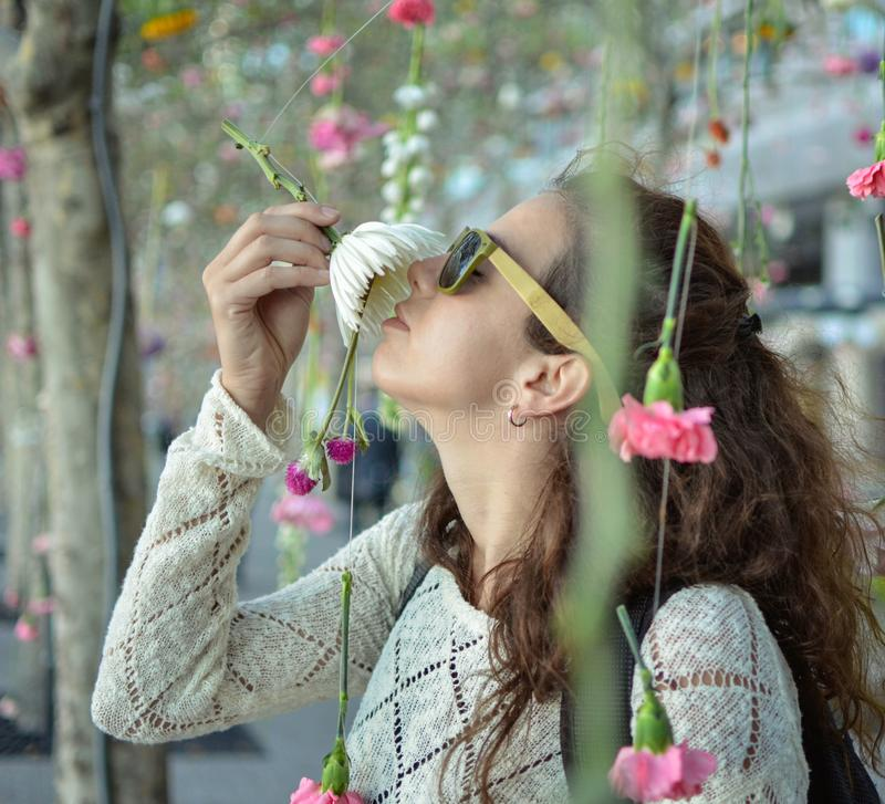 Girl smelling flowers hanging from the trees stock image