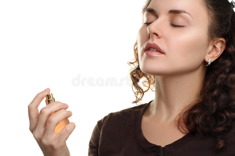 Girl is smelling the perfumes. The girl is smelling the perfumes are in her hand isolated on white background royalty free stock images