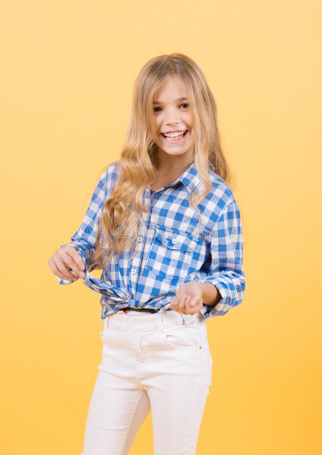 Girl smile in blue plaid shirt and white pants. Happy child with blond long hair on orange background. Kid fashion, beauty, style, look concept royalty free stock images