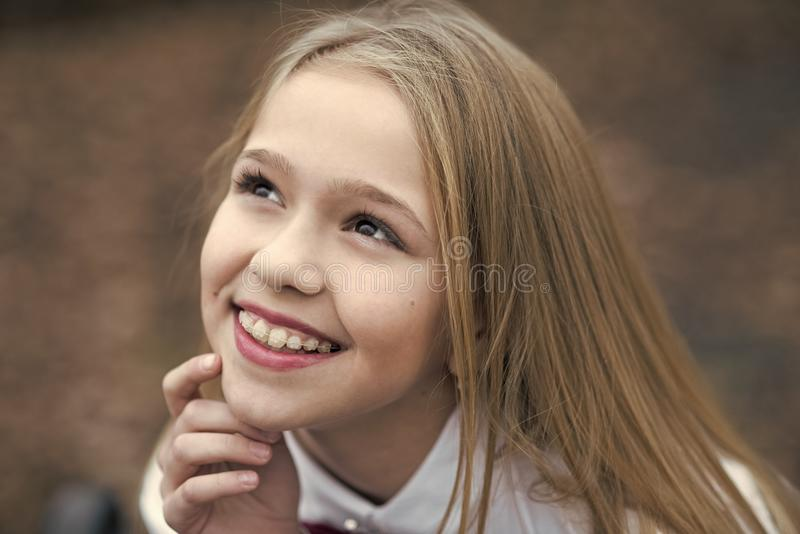 Girl smile with cute face, beauty. Little child smiling with long blond hair, hairstyle outdoor. Baby beauty, hair and royalty free stock photography