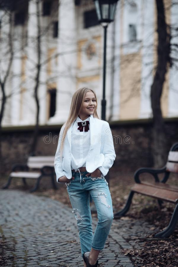 Girl smile in fashionable jeans in park, fashion. Little child with long blond hair outdoor, beauty. Baby beauty look royalty free stock images