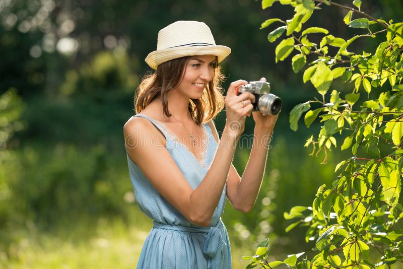 A girl with a smile in a forest or park with a camera takes pictures stock photo