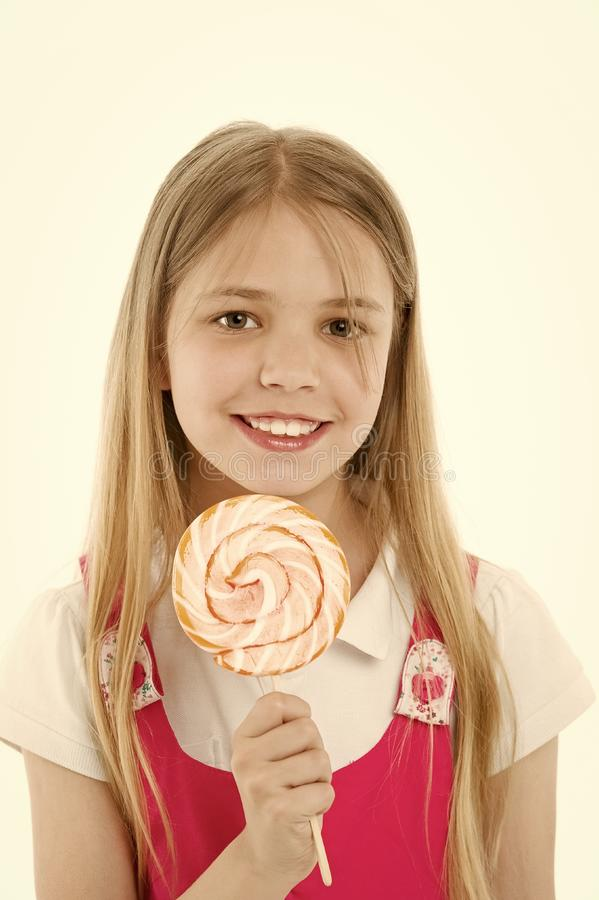 Girl smile with lollipop isolated on white. Small child smiling with candy on stick. Happy kid with swirl caramel. Food. And dessert. Enjoying sweet lollipop stock image