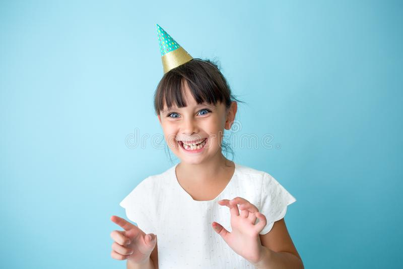 Girl with a with smile at party. Happy girl with a cone party hat. She has big blue eyes royalty free stock image