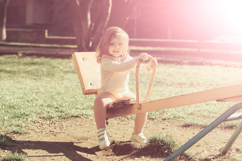 Girl smile on seesaw on sunny day royalty free stock photo