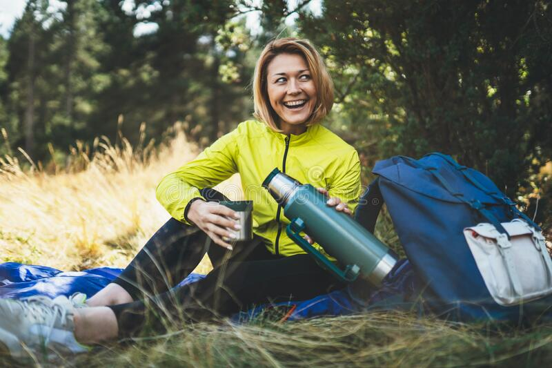 Girl smiles drink coffee thermos on nature after training, woman hold mug of warm tea outdoors, hiker laughing enjoys breakfast royalty free stock images