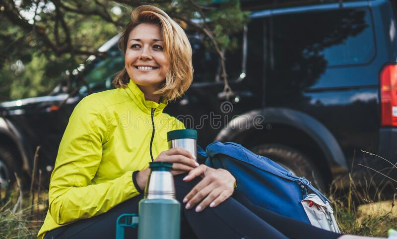 Girl smiles and enjoys nature hold hand mug of warm tea during recreation trip, hiker laughing showing teeth drink coffee stock photo