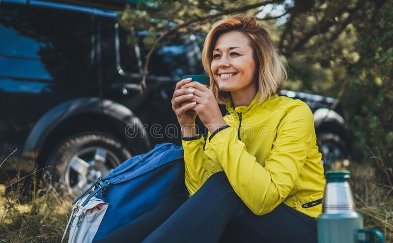 Girl smiles and enjoys summer nature hold hand mug of warm tea during recreation trip, happy hiker laughing showing teeth royalty free stock photography