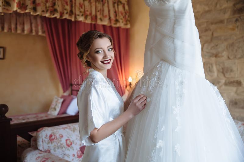 The girl smiles and shows her girlfriend her chic wedding dress. Make-up and hairstyle the bride has already done. She stock image