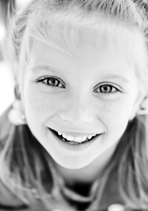 Girl smiling. Beautiful little girl smiling. Black and white royalty free stock photo