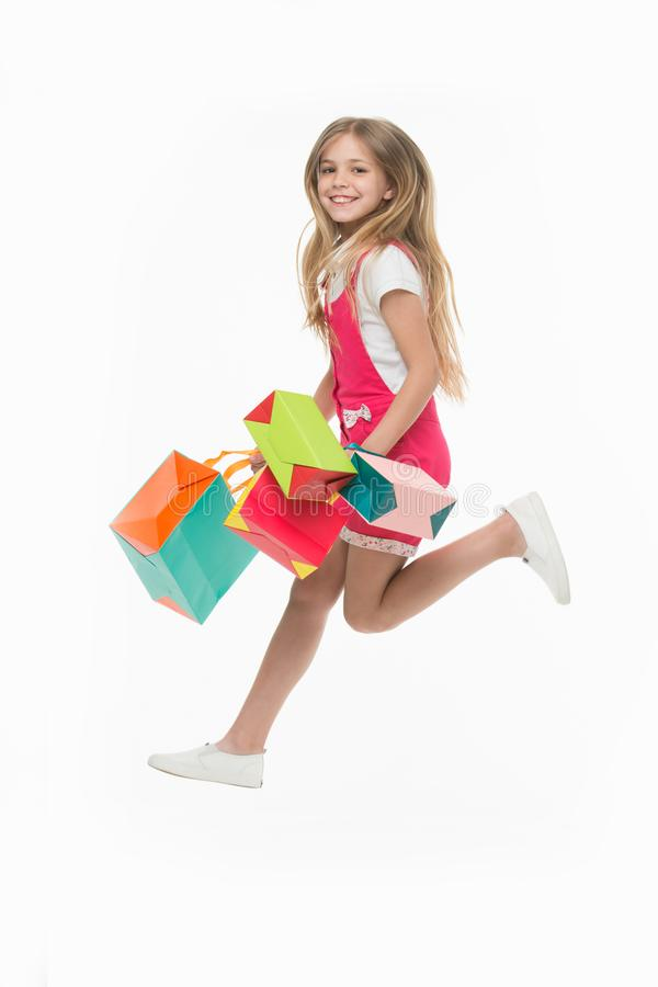 Girl on smiling face carries bunches of shopping bags, isolated on white background. Kid girl with long hair fond of. Shopping. Shopping concept. Girl likes to stock photos