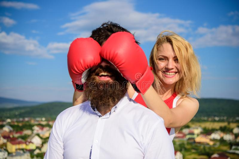Girl smiling face covers male face with boxing gloves. Cunning tricks to win. Guess who game. Relations game or struggle royalty free stock photography