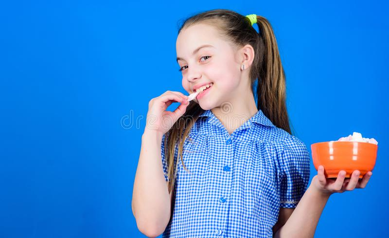 Girl smiling face hold bowl sweet marshmallows in hand blue background. Kid girl with long hair likes sweets and treats royalty free stock photo