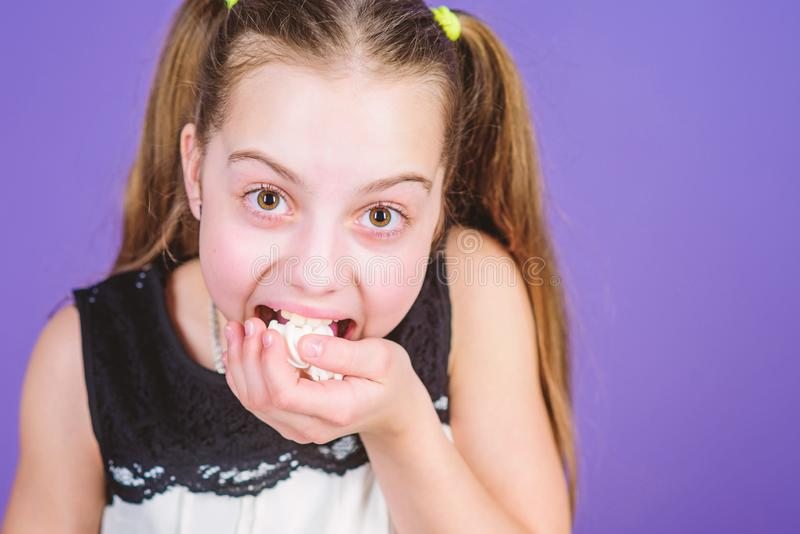 Girl smiling face holds sweet marshmallows in hand violet background. Sweet tooth concept. Kid girl with long hair likes. Sweets and treats. Calorie and diet royalty free stock photo