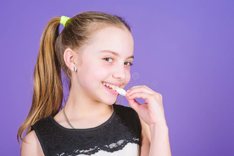 Girl smiling face holds sweet marshmallows in hand violet background. Sweet tooth concept. Kid girl with long hair likes stock image