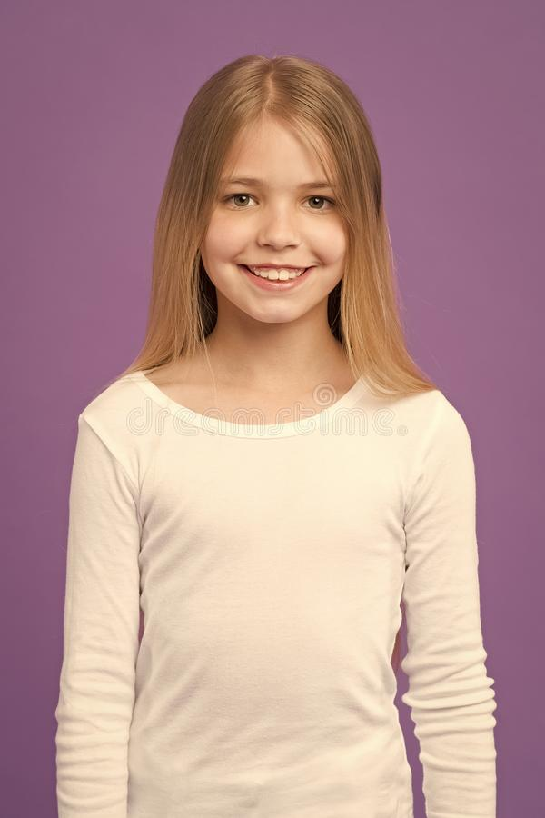 Girl on smiling face with long hair wears white shirt, violet background. Kid girl with long hair looks adorable royalty free stock photo