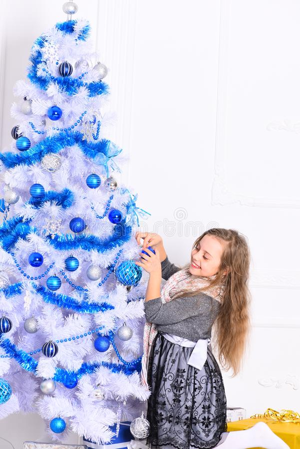 Girl with smiling face near white and blue Christmas tree stock image