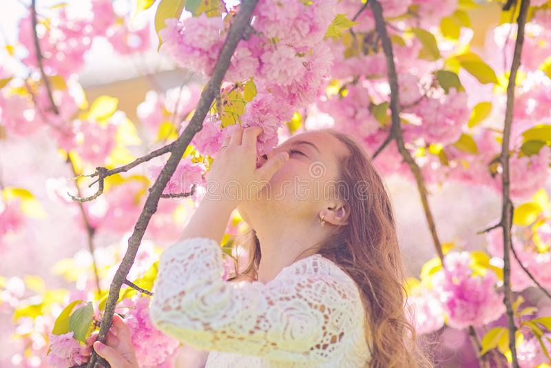 Girl on smiling face standing near sakura flowers, defocused. Perfume and fragrance concept. Cute child enjoy aroma of. Sakura on spring day. Girl with long stock photo