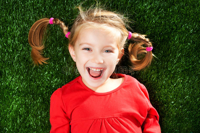 Girl smiling on grass. Girl smiling on a green lawn stock image