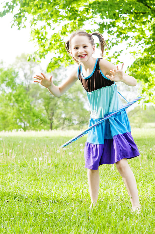 Girl smiling with hoola-hoop. Girl in country playing with hoola-hoop toy stock photo