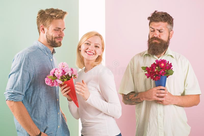 Girl smiling made her choice. Girl popular receive lot male attention. Broken heart concept. Men competitors with. Bouquets flowers try conquer girl. Woman royalty free stock photo