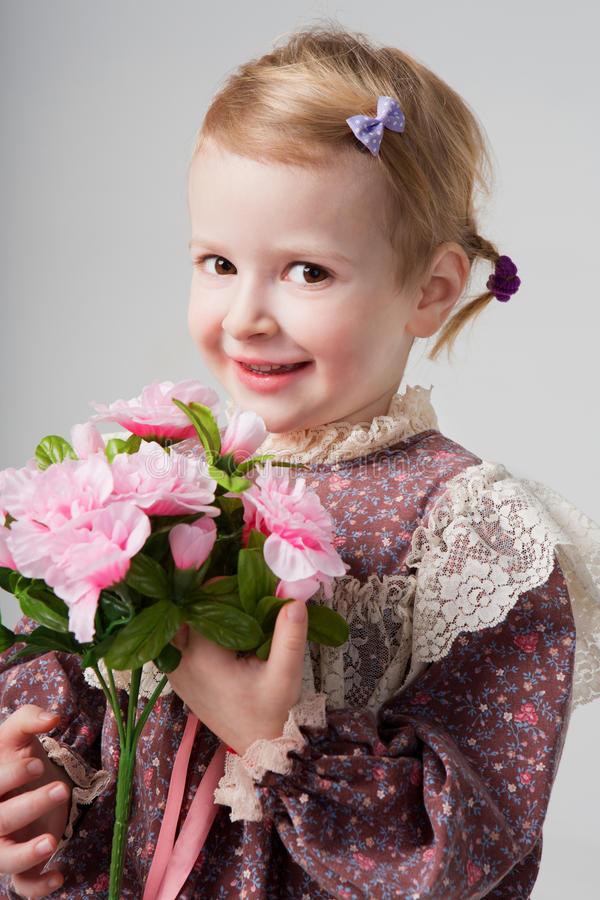 Girl smiling with pink flowers. Beautiful little lady holding bouquet on gray background stock photos