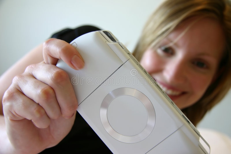 Girl smiling and playing handheld game console stock images