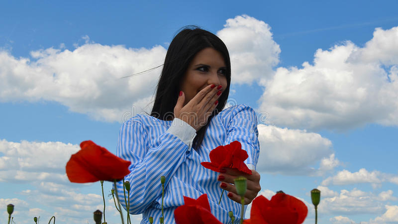 Girl is smiling in the poppy field of flowers royalty free stock image